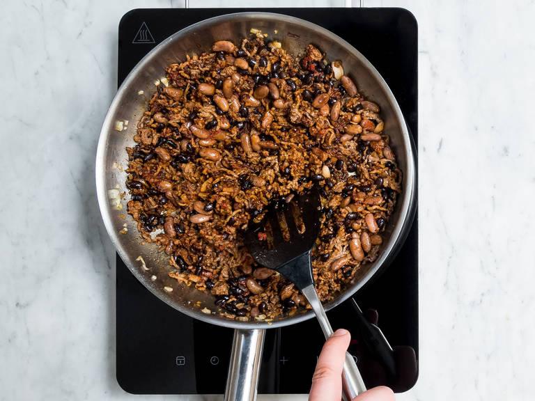 Backofen auf 180°C vorheizen. Zwiebel schälen und fein hacken. Pintobohnen und schwarze Bohnen abgießen und abspülen. Olivenöl in einer Pfanne erhitzen und die Zwiebel darin anschwitzen. Rinderhackfleisch zugeben und ca. 1 – 2 Min. braten. Chilipulver, Paprikapulver, Kreuzkümmel, Cayennepfeffer, Oregano und Zucker zugeben und mit Salz und Pfeffer abschmecken. Alles gut vermengen und für weitere ca. 2 – 3 Min. braten. Bohnen und Tomatenmark unterrühren und die Pfanne vom Herd nehmen.