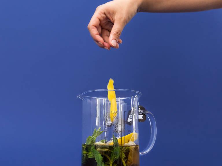 Währenddessen Wasser in einem Wasserkocher oder auf dem Herd zum Kochen bringen. Teebeutel, Minze und Zitronenschale in eine Kanne geben und mit heißem Wasser aufgießen. Für ca. 5 Min. ziehen lassen. Teebeutel, Minze und Zitronenschale herausnehmen und den Tee leicht abkühlen lassen.