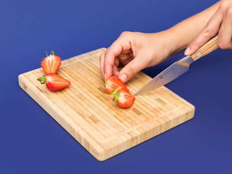 Restliche Erdbeeren halbieren und zum Servieren beiseitelegen.