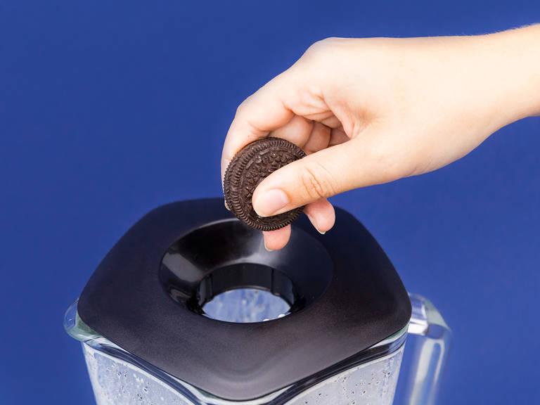 将半份奥利奥曲奇放入搅拌机中,搅打至完全融合。再放入剩余的曲奇,稍微搅打几秒钟,打成粗糙的大颗粒。