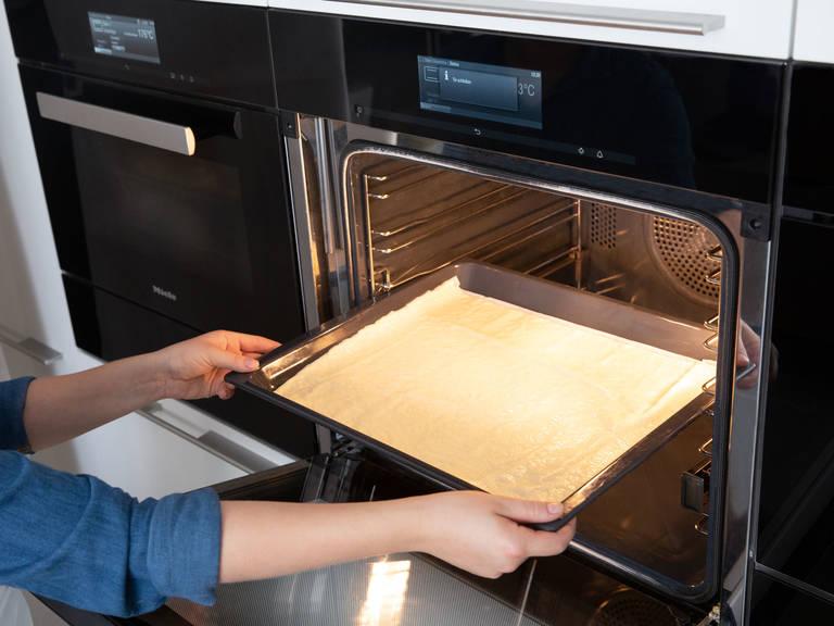 擀好披萨面团,将它放到烤盘中。放入烤箱,以240℃烤10分钟(无馅料),或直至面团变成棕色。