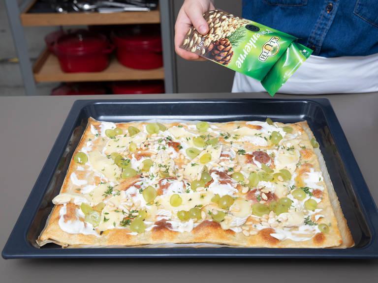 将披萨从烤箱中取出,抹上奶油奶酪,然后放上布里奶酪片和葡萄,淋上蜂蜜,撒上百里香叶片和松子。撒盐与胡椒调味。
