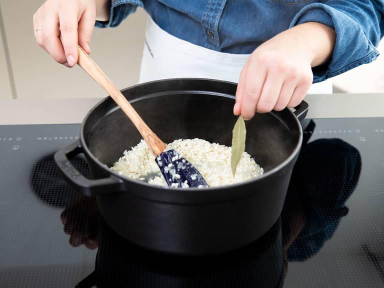 往里倒入半份白葡萄酒,中低火煮至葡萄酒完全挥发。先放入月桂叶,然后交替着一勺勺地倒入剩余的白葡萄酒和鱼肉高汤,每次都需待上一份汤汁被完全吸收,再倒入下一份。持续搅拌。