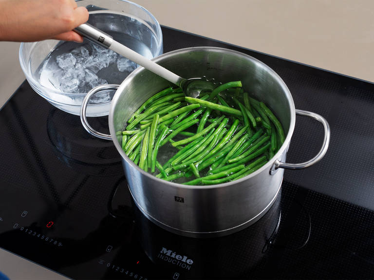 Trim green beans. Boil a large pot of water with plenty of salt. Blanch green beans for approx. 2 min., then transfer to a bowl of ice water to stop the cooking process. Remove from water, transfer to another bowl, and set aside.