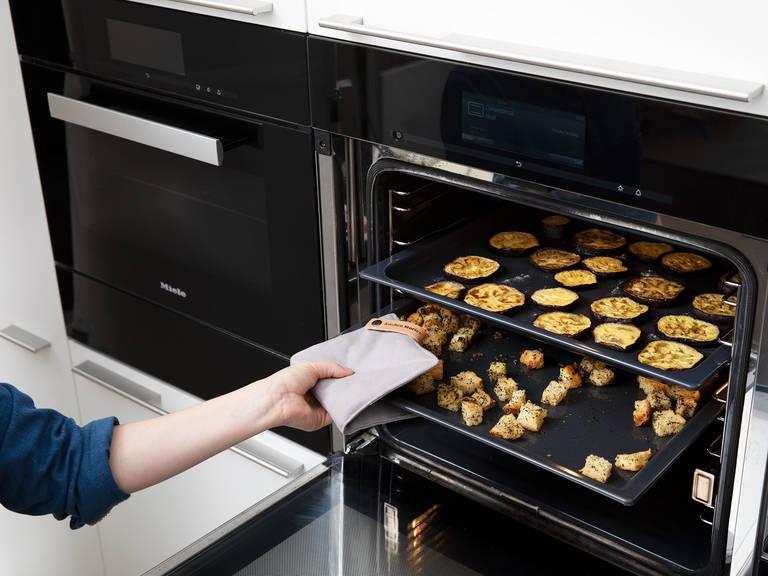 烤面包期间,将茄子两端切去,然后切成厚片,撒盐调味。将茄子片放到烤盘中,刷上橄榄油,放到烤箱中,以180℃烤35分钟,或直至茄子变软或烤熟。烤好后,将面包从烤箱中取出,置于一旁放凉。
