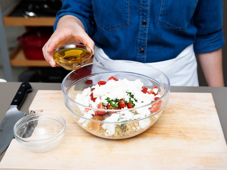 To make the tomato and bread salad, quarter the cherry tomatoes and place into a serving bowl. Slice basil into thin ribbons, crumble in the feta cheese, add olive oil, and season with salt and pepper. Toss well and set aside.