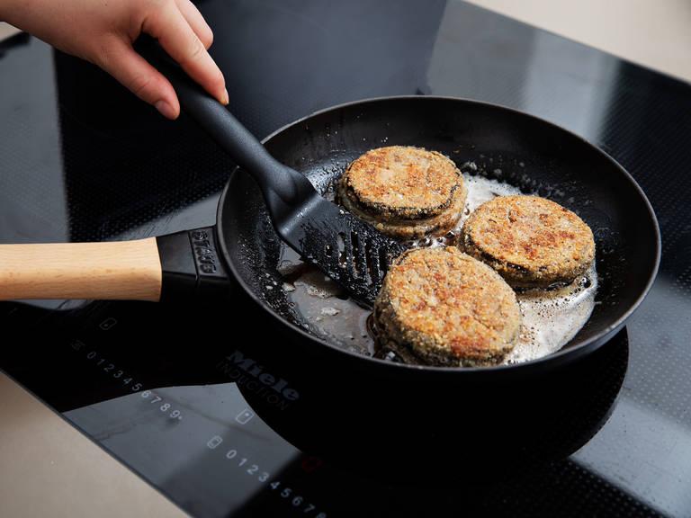 中高火加热大锅,倒入植物油预热。放入一大份奶酪夹心茄盒,每面煎2-3分钟,或直至茄子变成金棕色。将它们从锅中取出,放到厨房纸上吸干多余油分,然后佐以番茄面包沙拉,尽情享用吧!