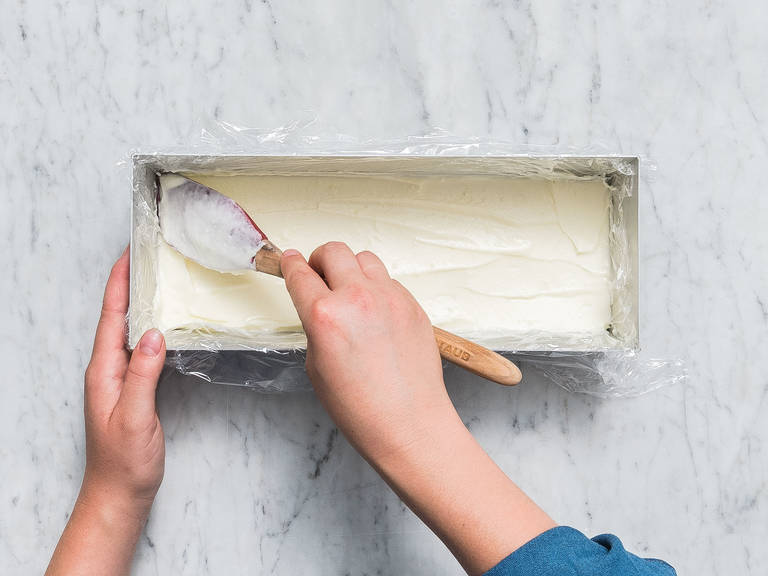 将海绵蛋糕从硅胶烤模上取出,切成两片,长度参照长烤盘的大小。往长烤盘里铺上塑料膜,先放入一块海绵蛋糕,抹上半份马斯卡波尼乳酪,冷藏。