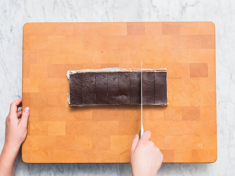 将长烤盘从冰箱中取出,倒出冰盒蛋糕,揭掉塑料膜。将蛋糕切成大小均等的巧克力棒,约9*3厘米,然后放到冷却架上。