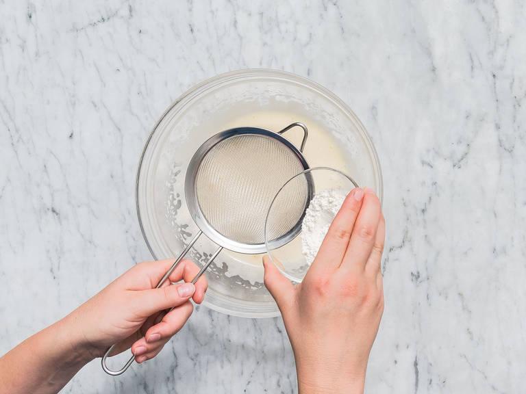 In der Zwischenzeit den Backofen auf 180°C vorheizen. Ei und restlichen Zucker mit dem Handrührgerät ca. 4 Min. schaumig schlagen. Mehl in die Schüssel sieben und vorsichtig unterrühren.