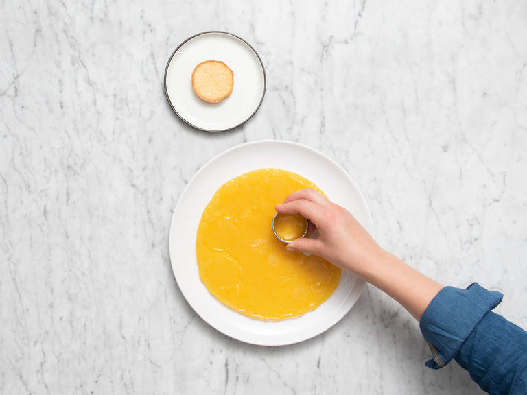 Remove orange jello from the fridge and cut out circles using a cookie cutter. Top each of the small sponge cakes with a piece.