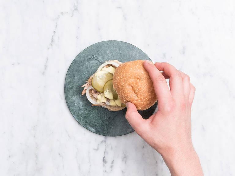 洋葱去皮切薄片。汉堡面包切半后用面包机烤一烤。在作为底层的面包上抹蜂蜜芥末酱,依次摆上手撕猪肉、洋葱圈、腌黄瓜,再淋依次蜂蜜芥末酱,盖上顶部的面包,尽情享用吧!