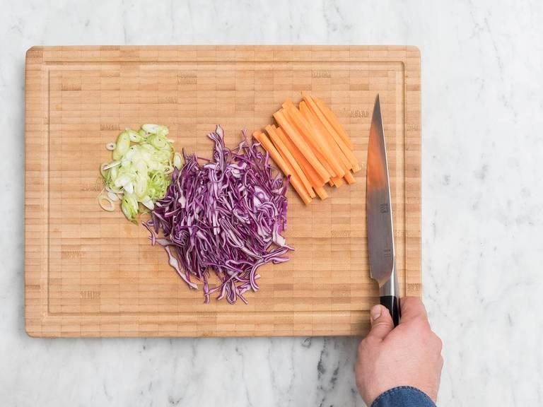 Reis in einen Topf geben, mit Wasser bedecken und für ca. 12 – 15 Min. kochen. Währenddessen Frühlingszwiebeln in feine Ringe schneiden, Rotkohl in dünne Streifen schneiden und Karotten schälen, halbieren und in dünne Stifte schneiden.