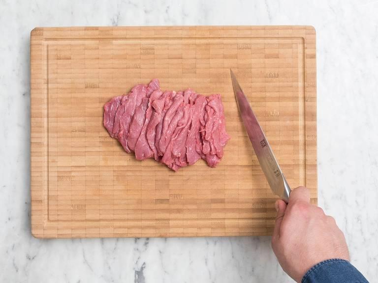 Überschüssiges Fett von der Rinderlende entfernen, trocken tupfen und in Streifen schneiden.