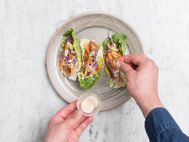 Blätter von den Salatherzen zupfen und auf einem großen Teller verteilen. Mit gekochtem Reis, Rindersteakstreifen, Karotten, Rotkohl und Frühlingszwiebeln belegen. Mit roter Thai-Currysauce und Sesam servieren. Guten Appetit!