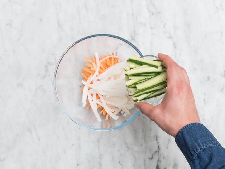 Währenddessen Karotten und Rettich schälen. Karotten, Rettich und Gurke in dünne Stifte schneiden. In eine weitere Schüssel geben und mit Reisessig, Sesamöl, Zucker und Salz vermengen. Die Enden der Chili entfernen und in dünne Ringe schneiden. Alles bis zum Servieren beiseitestellen.