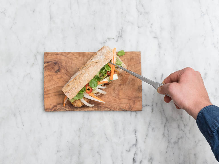 Cut off ends of baguettes and halve crosswise, then cut each piece lengthwise and spread Thai red curry sauce on both halves. Layer with sliced pork belly, quick pickled vegetables, chili slices, and cilantro. Enjoy!