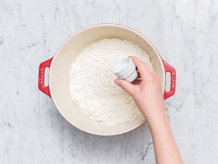 将温水、新鲜酵母和酸酵头倒入一个大碗中,搅拌至酵母溶解。往里加入面包粉、全麦斯佩尔特面粉和盐,用橡胶刮刀搅拌至形成柔滑面团。在25℃的环境中,静置40-45分钟。