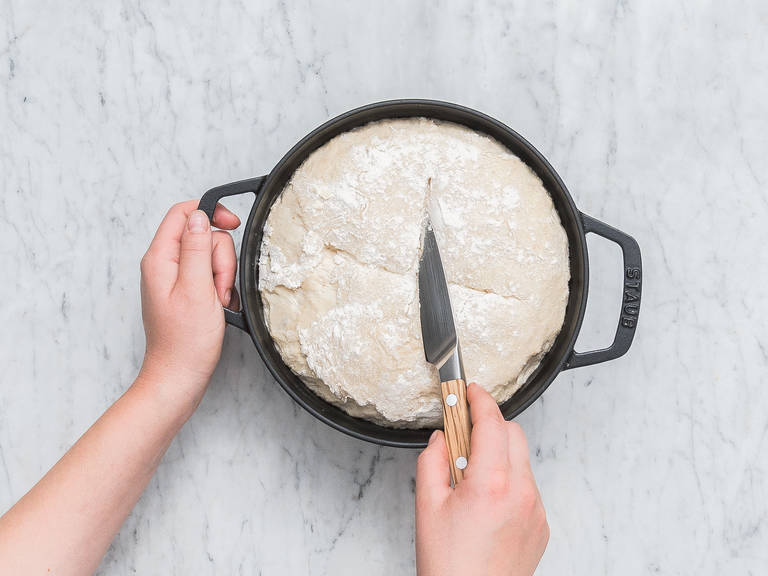 Backofen auf 250°C vorheizen. Ein tiefes Backblech auf die untere Schiene des Backofens schieben und mit etwas Wasser füllen. Ofenrost auf die nächst höhere Schiene schieben. Ein Kreuz in die Oberfläche des Teigs ritzen und den Topf in den Backofen stellen. Den Teig im gusseisernen Topf ca.  35 - 45 Min. backen, und dabei nach der Hälfte der Zeit die Backofentür einmal öffnen, um den Dampf entweichen zu lassen, danach wieder schließen. Das Brot aus dem Backofen nehmen und vor dem Anschneiden komplett auskühlen lassen. Guten Appetit!