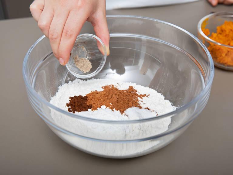 Temperatur des Backofens auf 175°C reduzieren. Walnüsse hacken und beiseitestellen. Mehl, gemahlenen Zimt, Muskat, Nelken, Kardamom, Backpulver, Backnatron und Salz in eine Schüssel geben und vermengen.