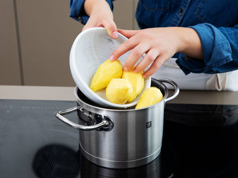 In the meantime, peel potatoes and add them to a pot with water. Cook until soft, then drain, and transfer them to a large bowl. Mash the potatoes until they are smooth.