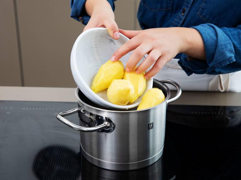 此期间,将土豆削皮,放到一锅水中。煮至土豆变软,捞出放到一个大碗中。用捣泥器将土豆捣烂。