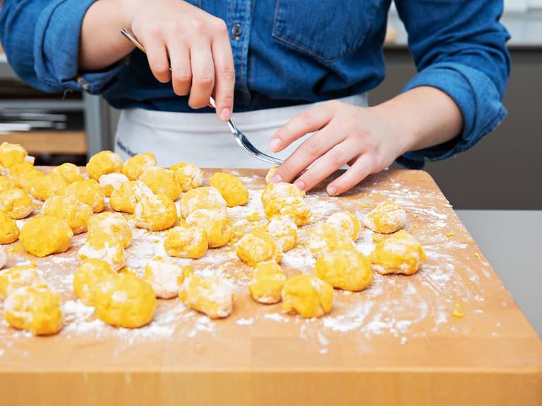 在一个干净的工作台上撒面粉,放上些许面团,揉成一个长条状。剩余的面团也重复这项操作。用叉子将面团挖成一个个团子的形状,放到撒了面粉的工作台上。