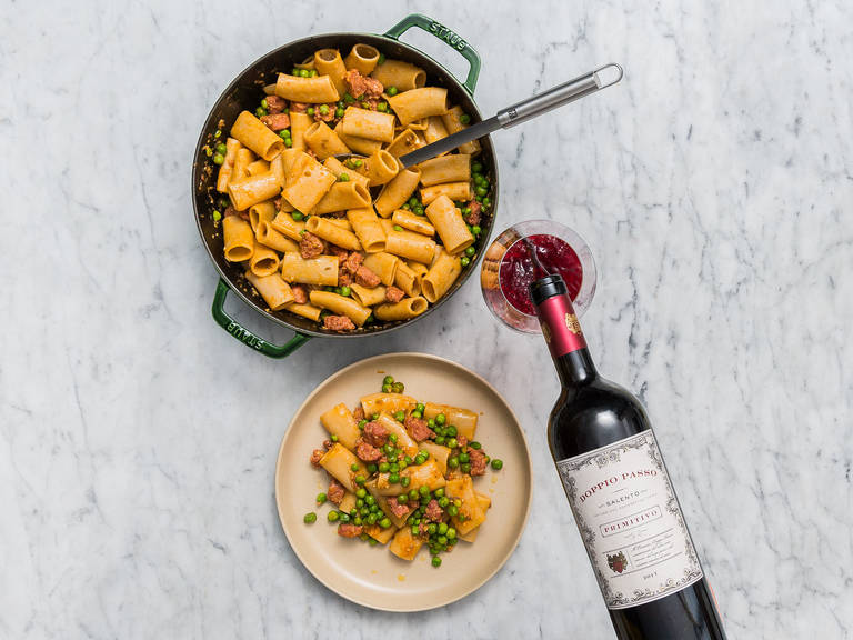 Add the drained pasta to the sauce along with the grated Parmesan cheese, a drizzle of olive oil, and stir to combine. Serve with extra Parmesan cheese, if desired, and pair the dish with a glass of red wine.