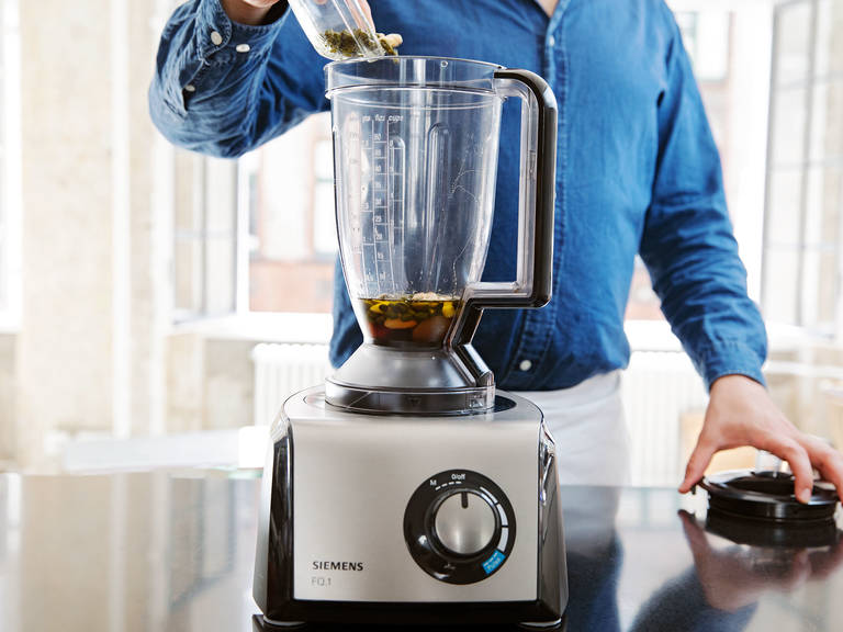 In a food processor, process the toasted nuts together with some more olive oil, dried apricots, amaretto, and half of the honey, until nuts are ground and mixture forms a coarse paste.