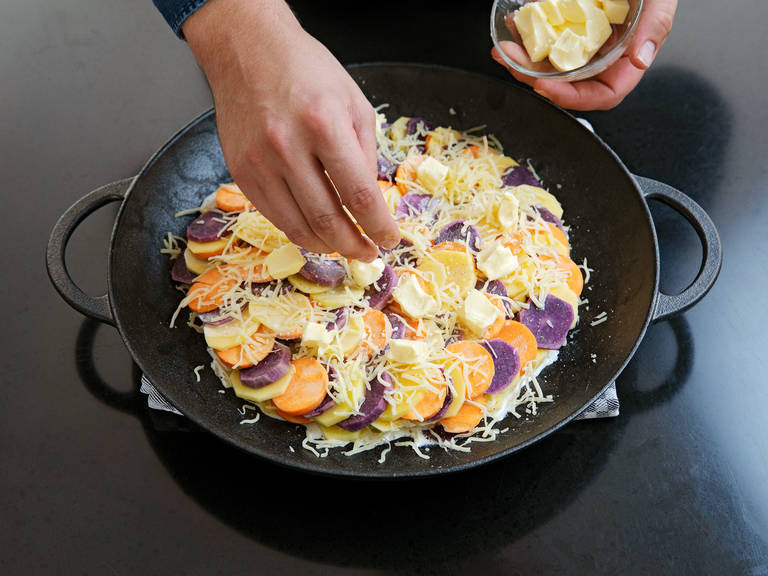 In a small bowl, mix finely chopped garlic with heavy cream and season to taste with salt, pepper, and ground nutmeg. Pour over potatoes and distribute butter in pieces on top.