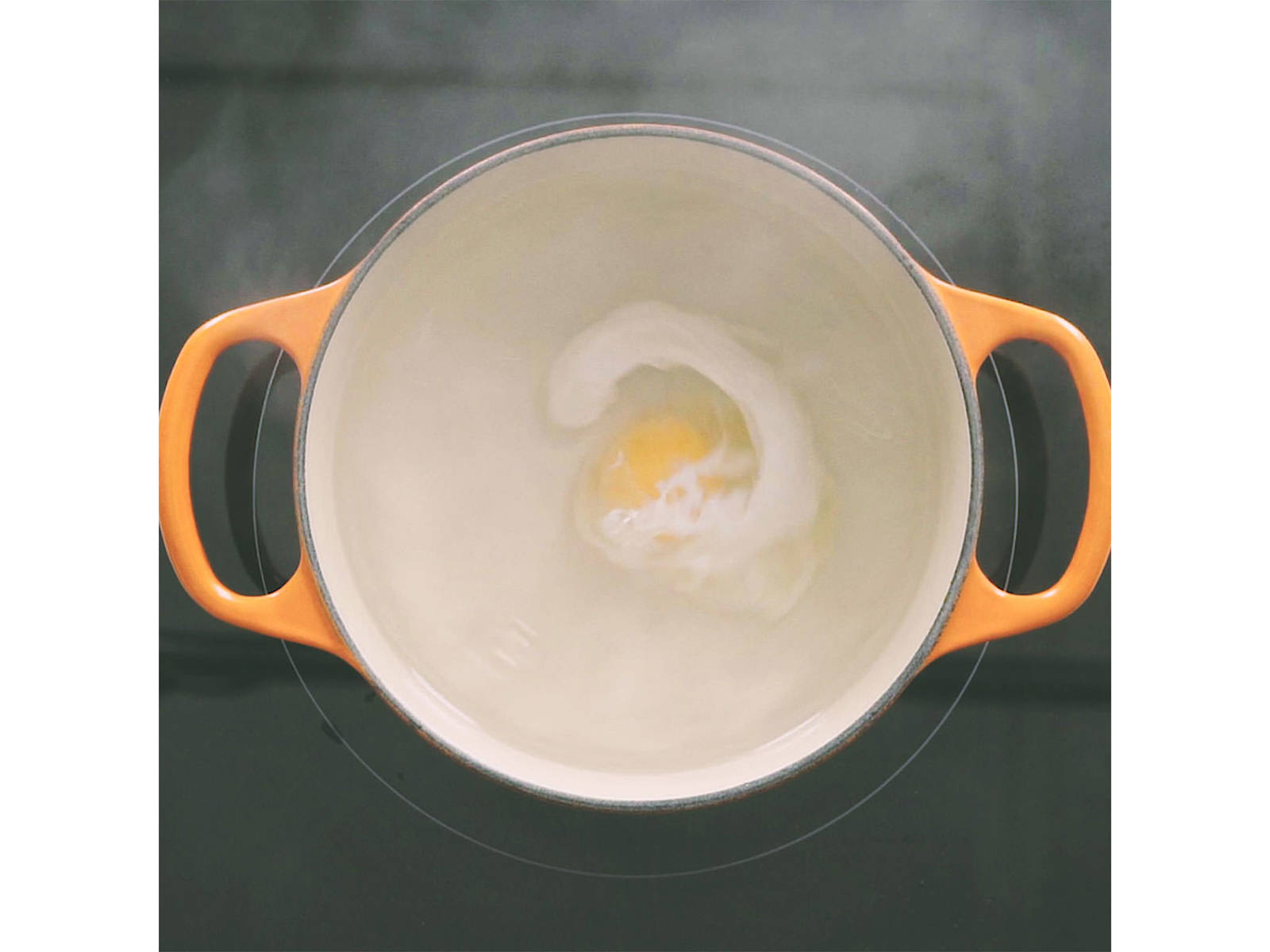Bring a medium pot of water to a simmer. Add salt and white vinegar. Use wooden spoon to create a whirlpool, then slowly add egg. Let cook until egg white is set, approx. 3 min.