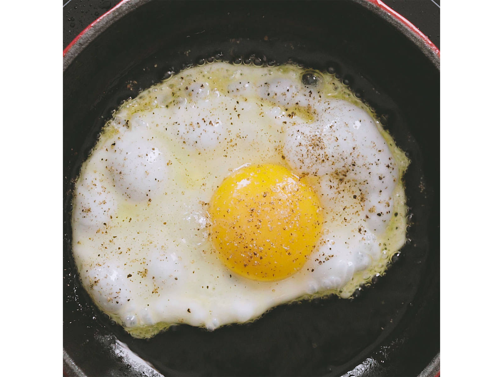 In a frying pan, heat olive oil over medium-high heat and fry egg. Season with salt and pepper.