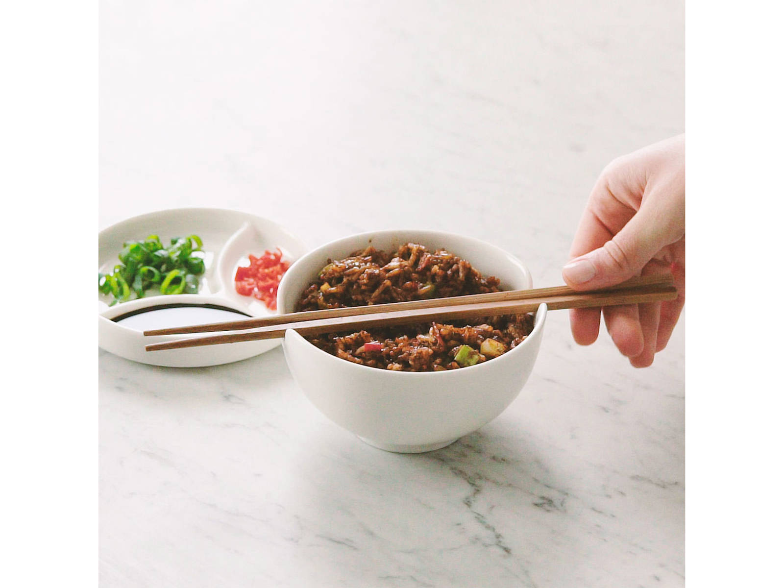 Transfer to a serving bowl and garnish with reserved scallion greens, fresh chili and soy sauce to taste. Enjoy!