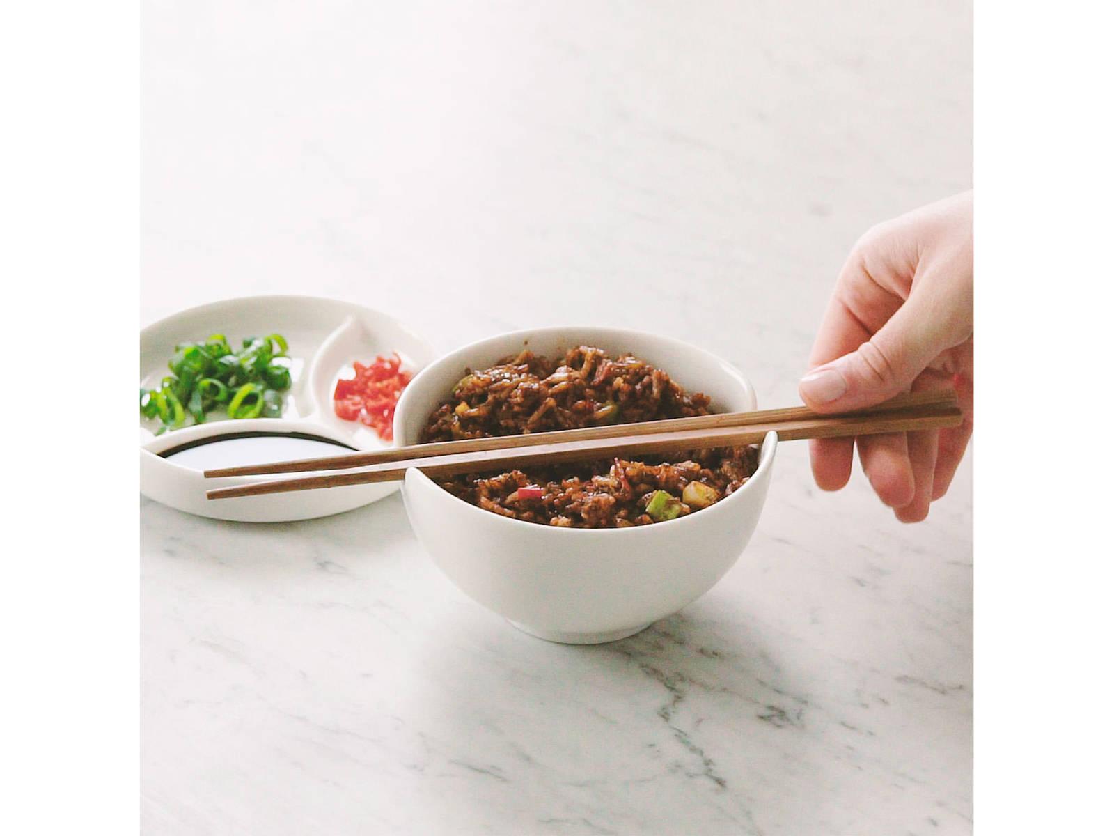 将炒饭倒进碗中,撒上辣椒末、葱绿末,淋上酱油。尽情享用吧!
