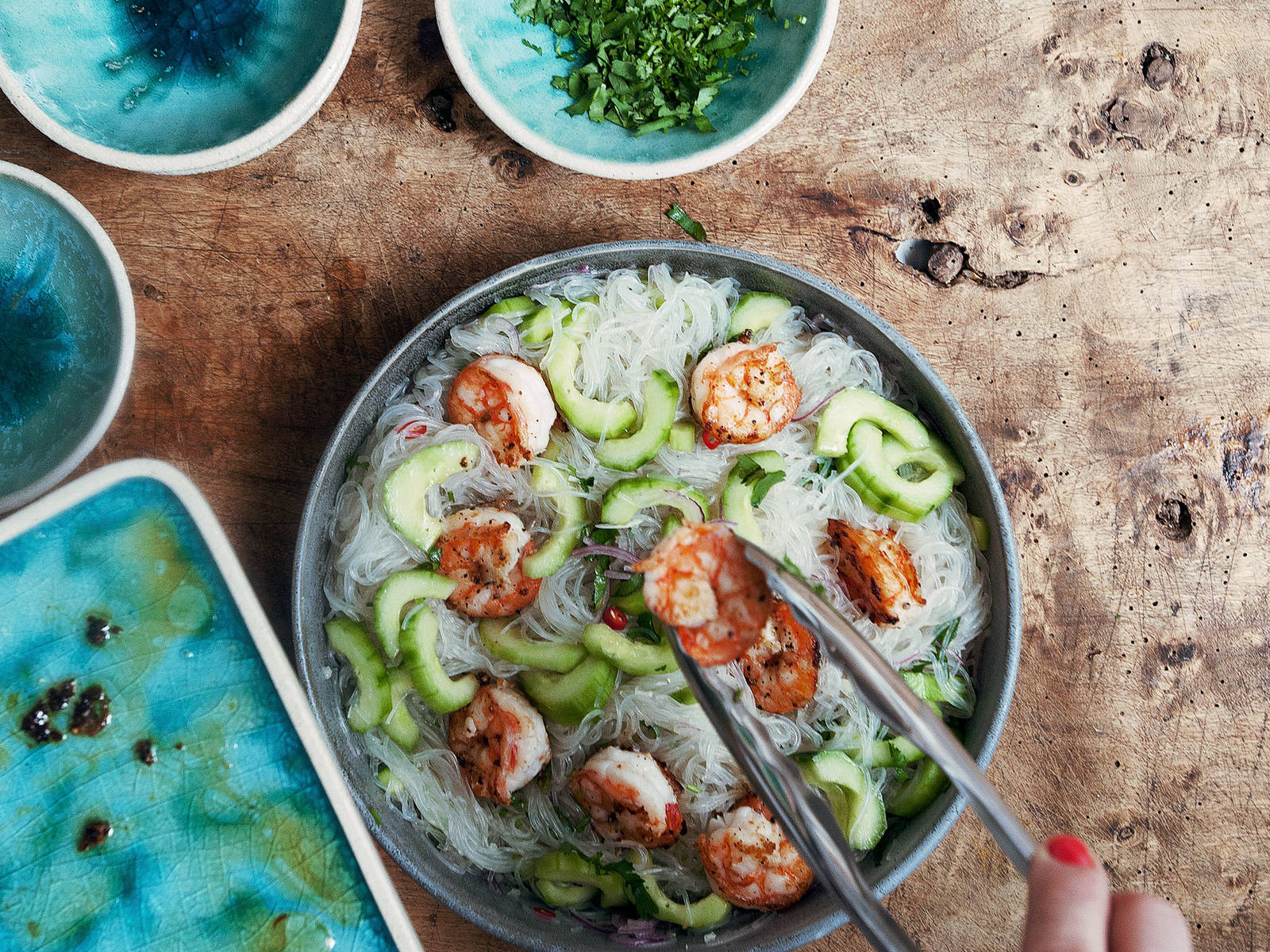 In a large bowl, combine cucumber, onion, garlic, chili pepper, toasted sesame oil, fish sauce, and lemon juice and toss. Add drained glass noodles to bowl along with shrimp. Mix everything thoroughly together. If desired, add more lime juice, sesame oil, or fish sauce to taste. Top with chopped coriander, serve and enjoy!