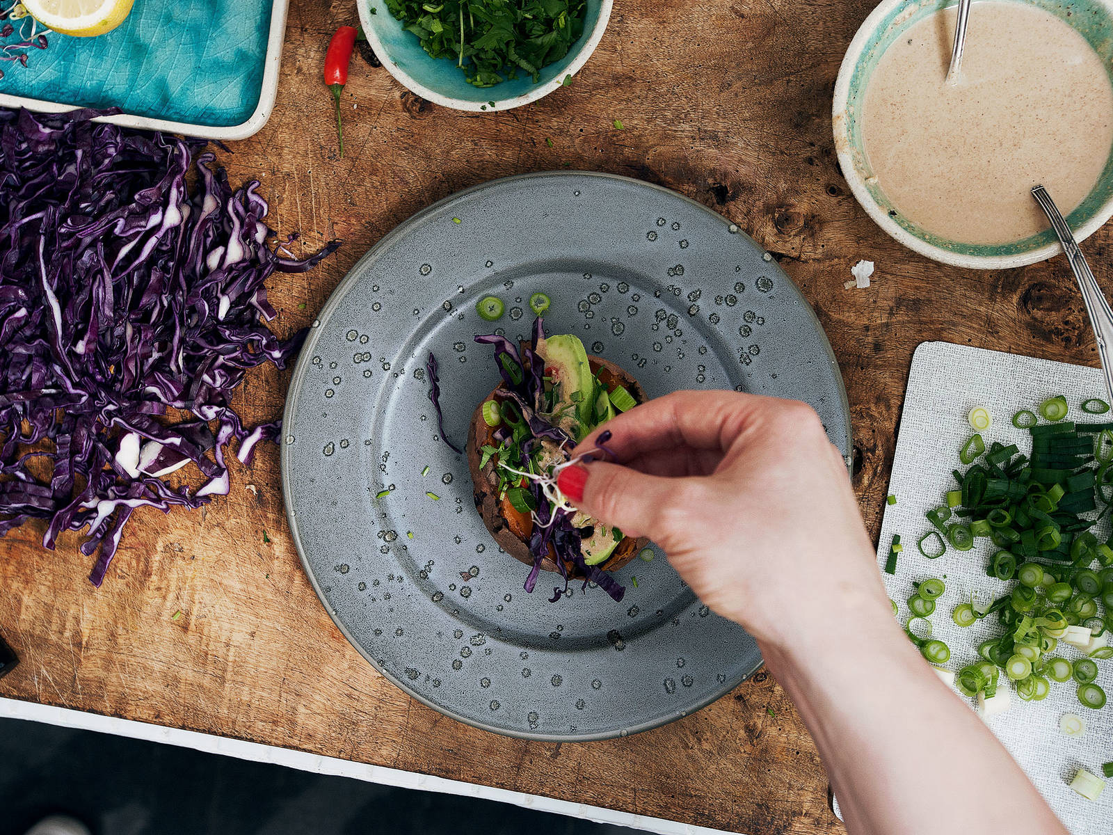 Remove potatoes from oven and top each with red cabbage, green onions, avocado, cilantro, and chili pepper. Drizzle with tahini-citrus sauce and enjoy!