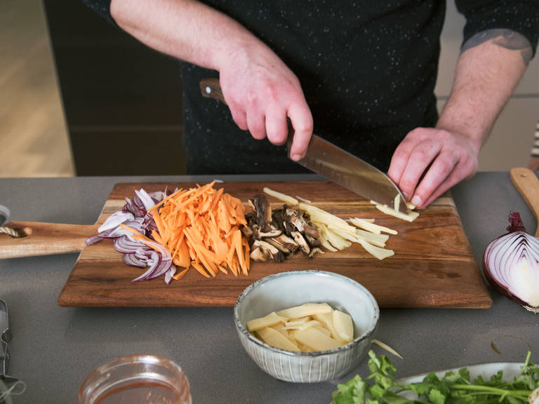 Peel and mince ginger and garlic. Finely chop cilantro roots. Remove seeds from Thai chilis and finely chop. Peel and halve onion, then cut it into fine rings. Finely dice shiitake mushrooms. Slice carrots and bamboo shoots and set aside.