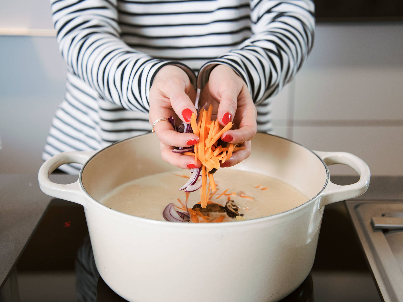 将椰奶混合物和蔬菜高汤一起倒入大平底锅中,搅拌均匀,煮沸。调至小火。放入切好的洋葱、香菇、胡萝卜和竹笋,煮10分钟。放入菠菜,浸入汤中,再煮5分钟。