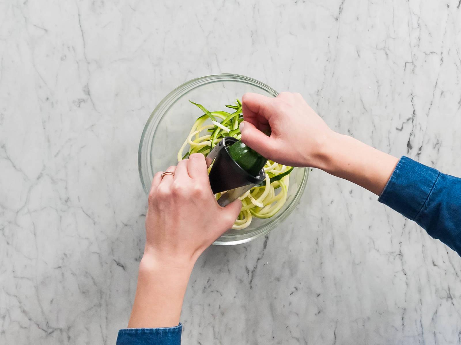 Zucchini mit einem Spiralschneider in dünne Spaghetti schneiden. Falls kein Spiralschneider vorhanden ist, kann auch ein Sparschäler benutzt werden.
