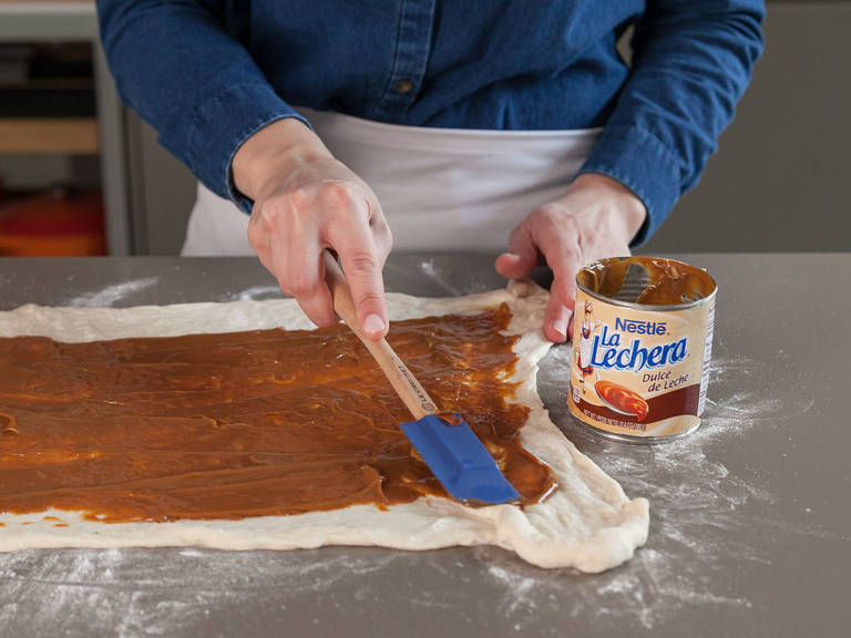 Heat the dulce de leche in a small saucepan set over low heat. Chop pecans and toast them in a small frying pan. Spread warm dulce de leche over dough, leaving a 2.5 cm/1 in. border. Dust with cinnamon. Sprinkle with toasted pecans, butter, and salt.