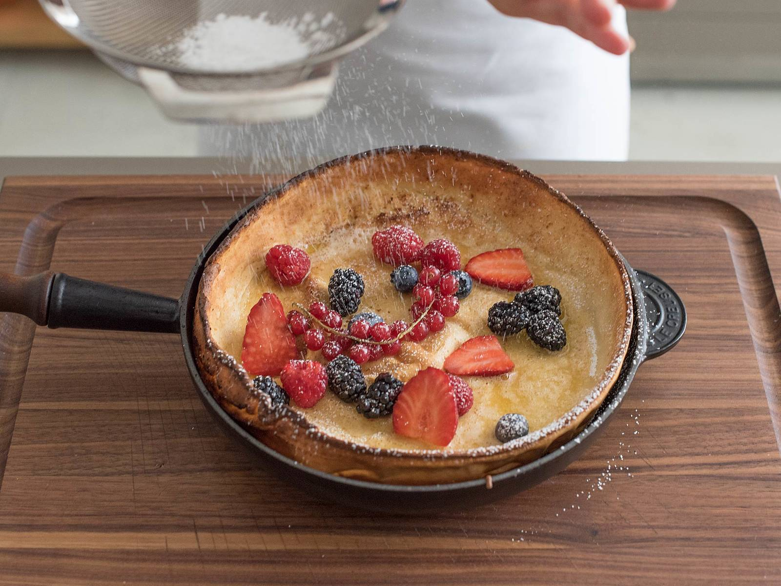 Slide Dutch baby onto serving platter or cutting board, or serve straight from pan, if desired. Top with fresh berries and sprinkle with lemon juice. Dust with confectioner's sugar and cut into wedges for serving. Serve warm with maple syrup.