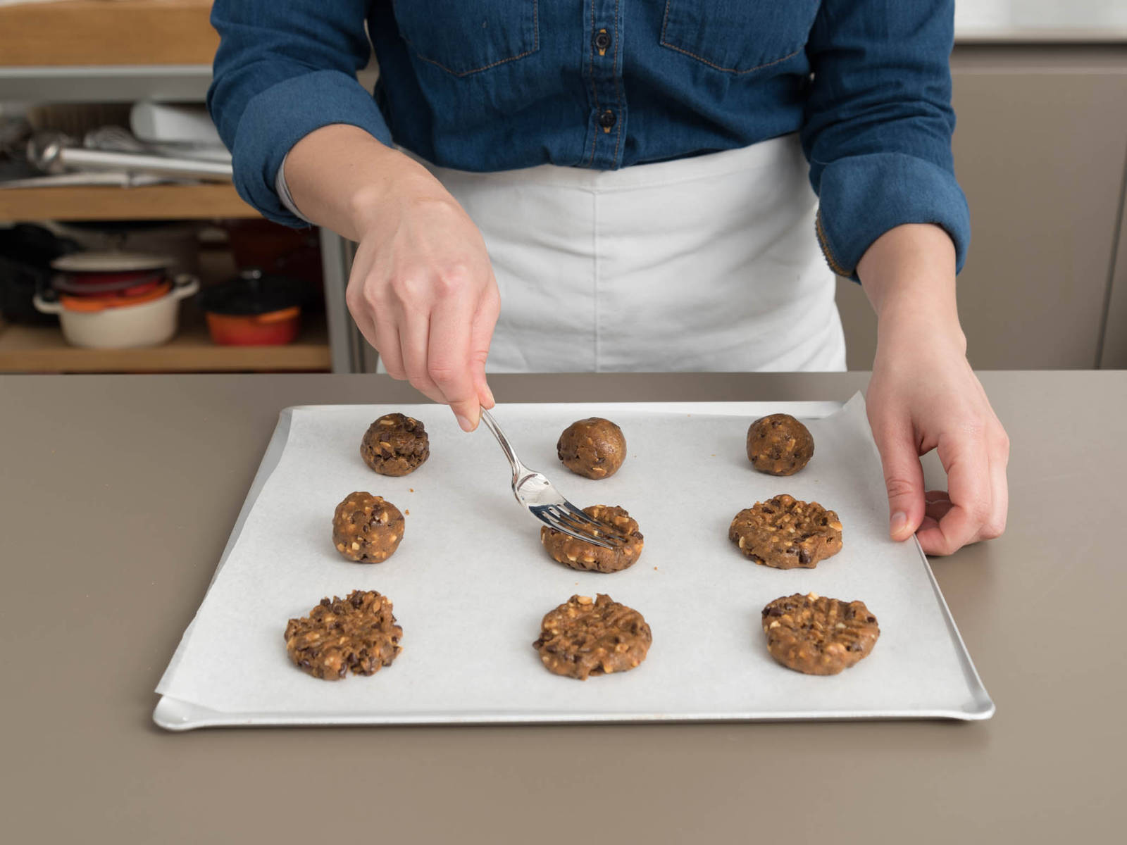 Scoop dough into equal-sized balls and place on parchment paper-lined baking sheets, spacing balls about 5 cm/2 in. apart. Use fork tines to flatten and make crisscross marks on cookies. Sprinkle with flaky sea salt, if desired.