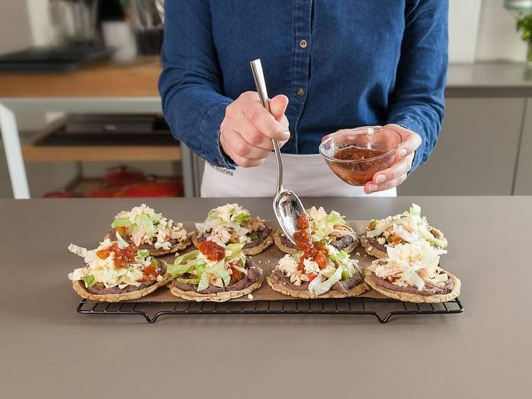 Top each sope with warm refried beans and the chicken and vegetable filling. Garnish with lettuce, grated queso fresco, and salsa to taste. Enjoy!