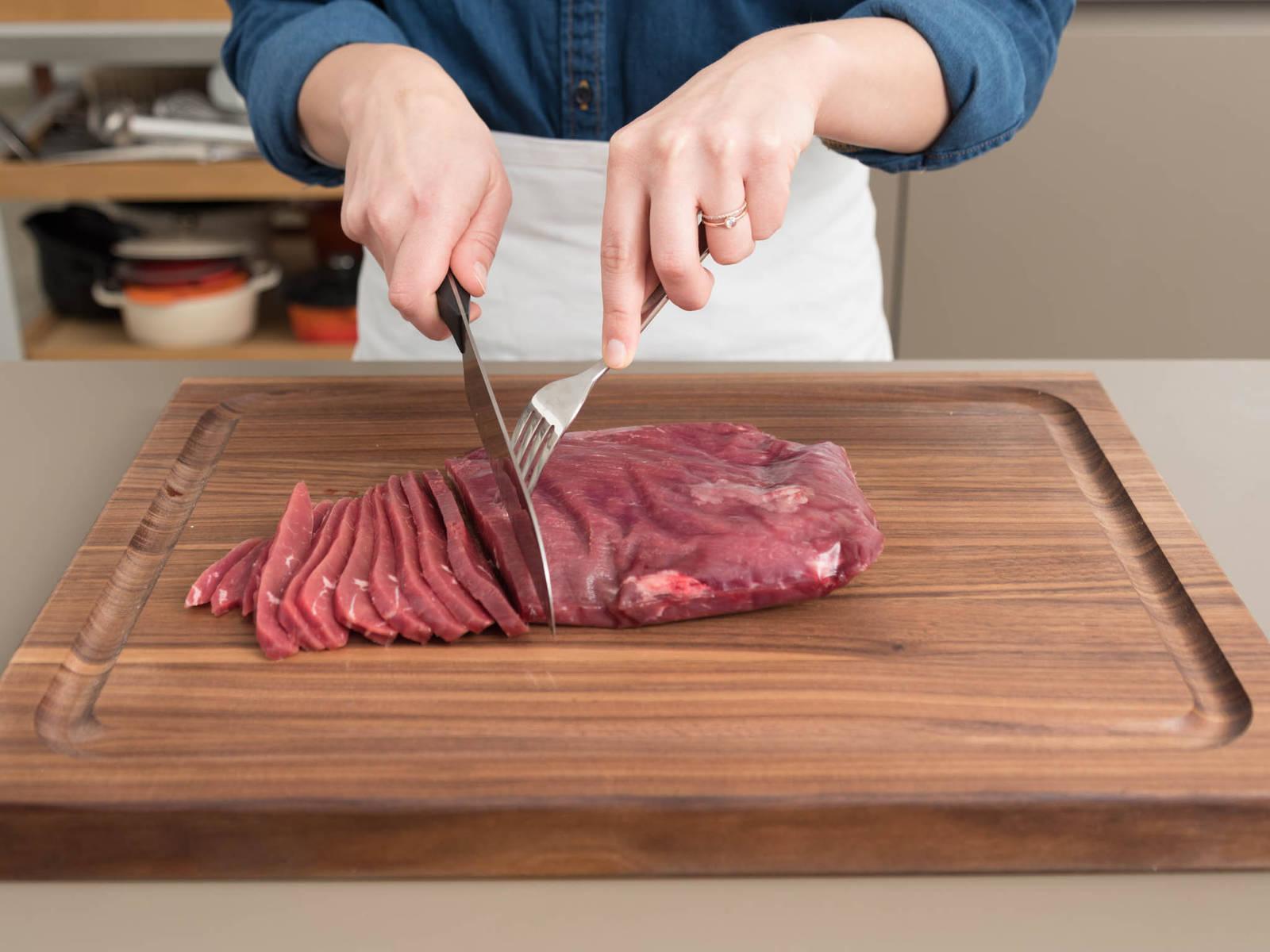 Fleisch in Frischhaltefolie wickeln und für ca. 1 Stunde einfrieren. Dadurch lässt sich das Fleisch leichter schneiden. Anschließend das Fleisch gegen die Faser in dünne Streifen schneiden und in eine große Schüssel oder einen verschließbaren Gefrierbeutel geben.