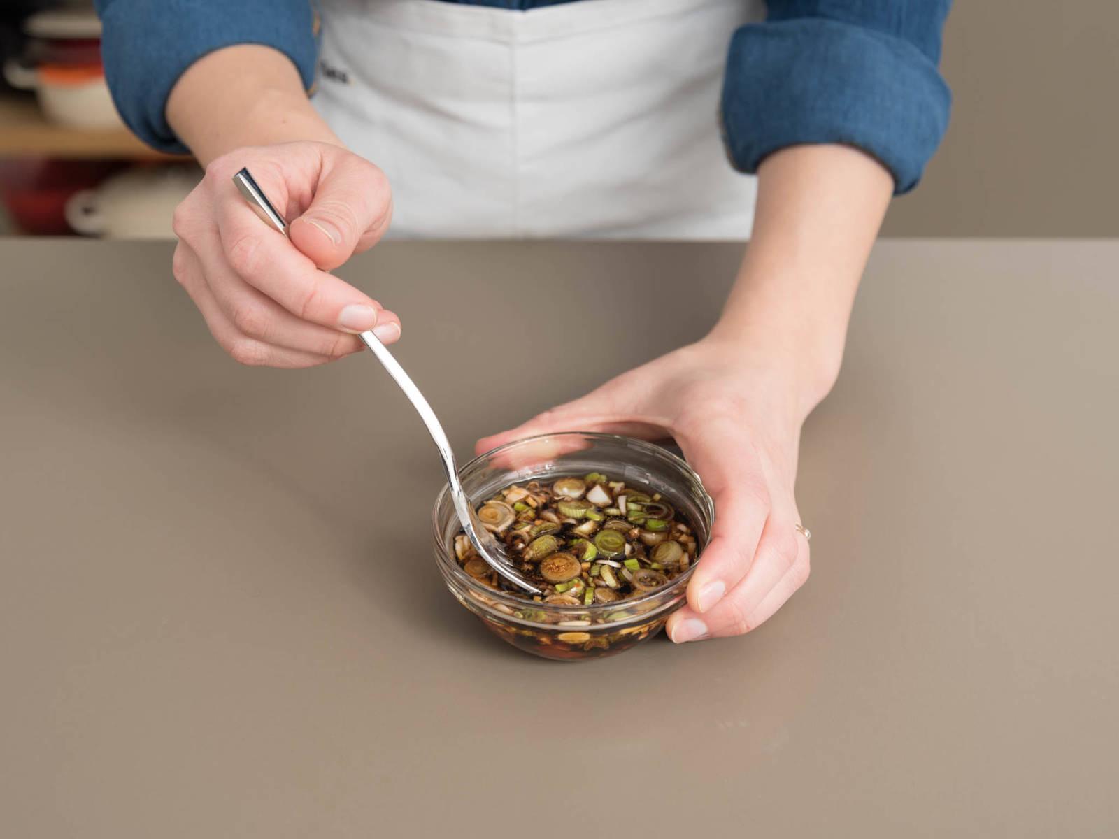 Knoblauch und Ingwer hacken. Sojasauce, Reiswein, Zucker, Sesamöl, Sriracha-Sauce, gehackten Knoblauch und Ingwer in einer kleinen Schüssel verrühren. Weißen und hellgrünen Teil der Frühlingszwiebeln in feine Ringe schneiden und zur Marinade geben. Den dunkelgrünen Teil der Frühlingszwiebel zum Servieren beiseitelegen.