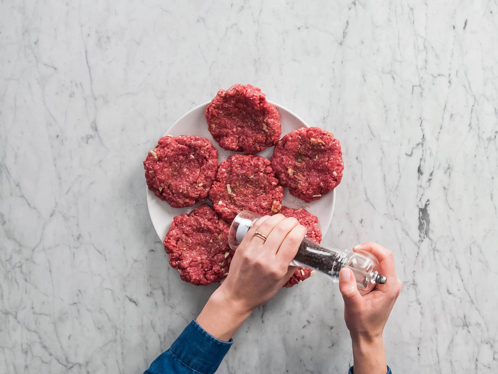 Preheat grill to medium-high. Mince garlic. Remove crusts from bread, dice, and mash with evaporated milk in a small bowl. Stir in Worcestershire sauce, salt, pepper, and garlic. Add bread mixture to beef with fork or hands, gently mixing together. Divide meat into portions and gently form into patties. Using thumb or fingertips, press shallow indentations in centers of patties. Season both sides of patties with salt and pepper, if desired.