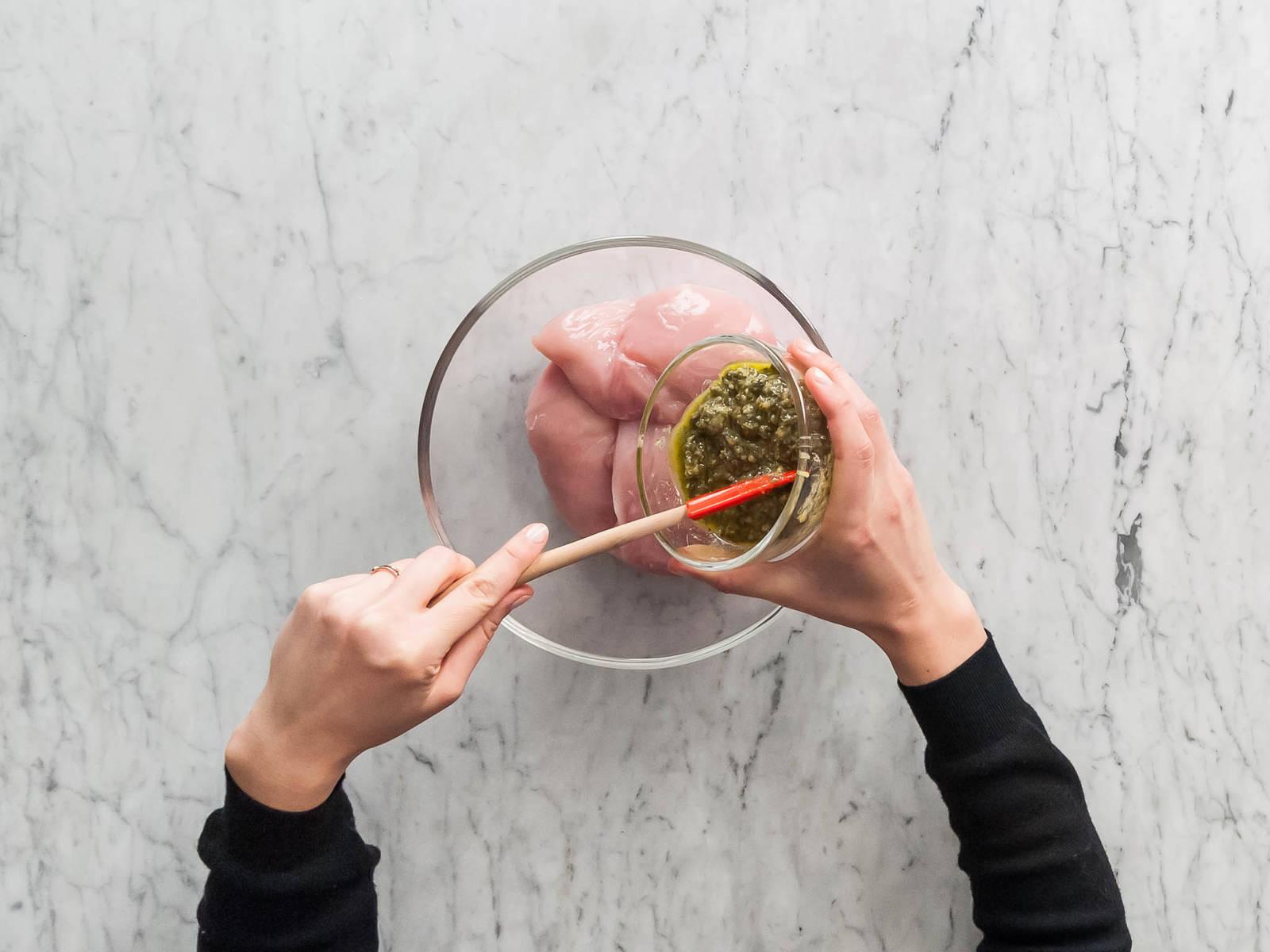 Backofen auf 200°C vorheizen. Tomaten in Scheiben schneiden. Hähnchenbrüste und Pesto in einer mittelgroßen Schüssel vermengen, bis das Fleisch rundherum mit Pesto bedeckt ist.