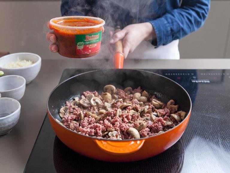Wein hinzufügen und mit einem Kochlöffel den am Topfboden klebenden Bratensatz lösen. Marinara-Soße hinzugeben und gelegentlich umrühren, bis sie aufgewärmt ist. Vom Herd nehmen.