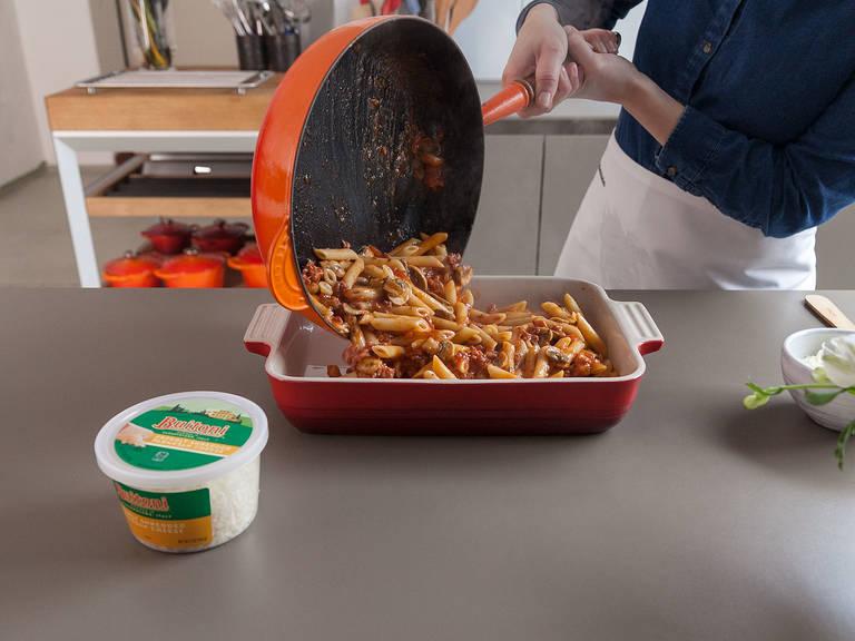 Gekochte Penne zur Soße geben und vermengen. In die vorbereitete gefettete Auflaufform füllen.