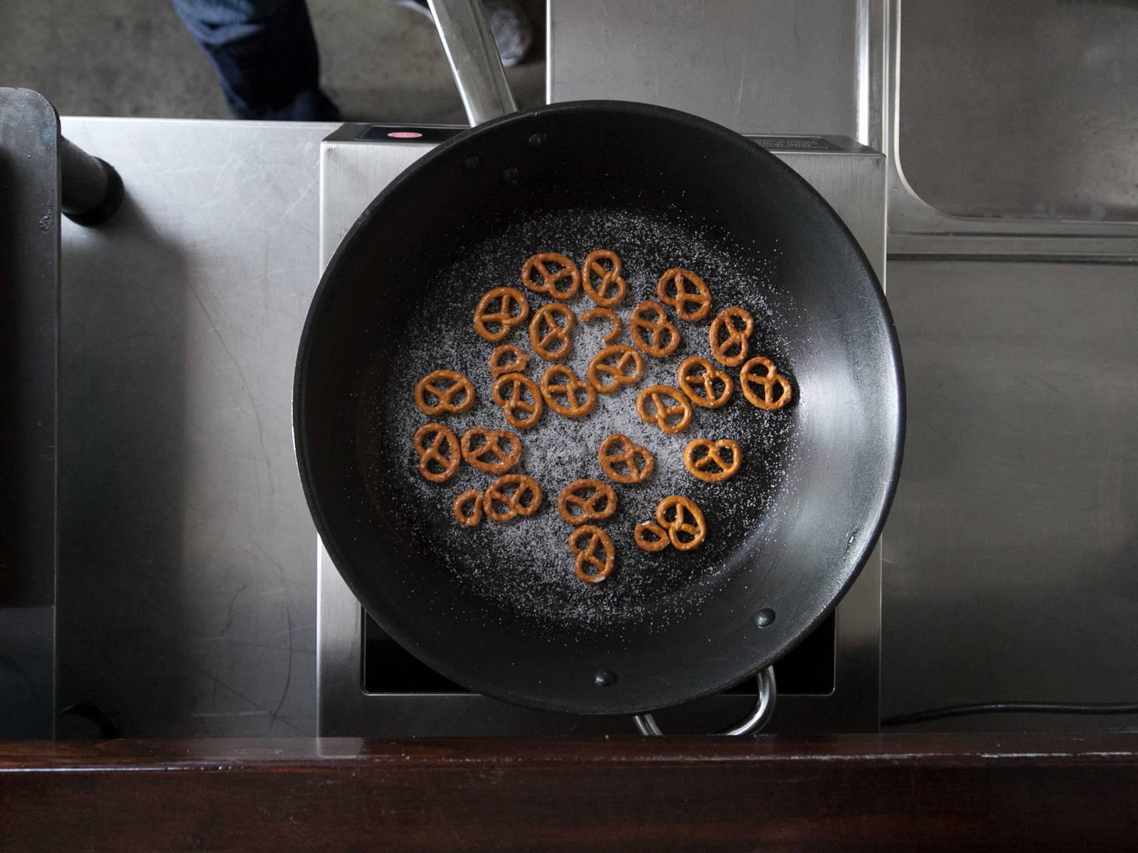 在不粘锅中,中火焦化砂糖,裹到咸味椒盐饼干上。注意别熬过火了。关火取下,放凉。将焦糖椒盐饼干拿出来,大略剁碎。